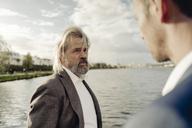 Senior businessman at a lake talking to man in foreground - KNSF03351