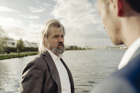 Senior businessman at a lake talking to man in foreground - KNSF03351
