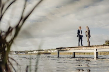 Two businessmen standing on jetty at a lake talking - KNSF03354
