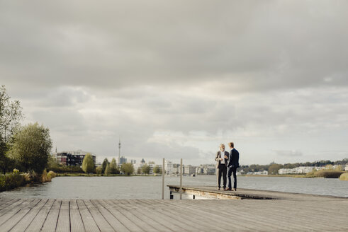 Two businessmen standing on jetty at a lake talking - KNSF03363