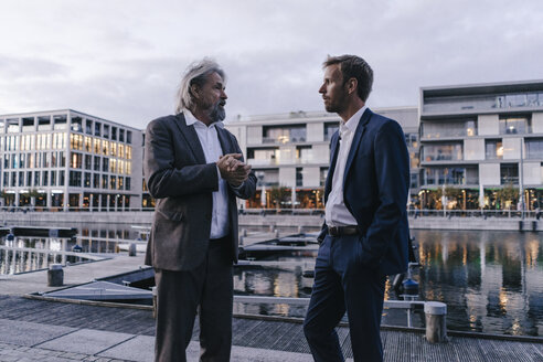 Two businessmen talking at city harbor at dusk - KNSF03375