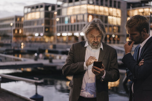 Two businessmen with cell phone at city harbor at dusk - KNSF03381