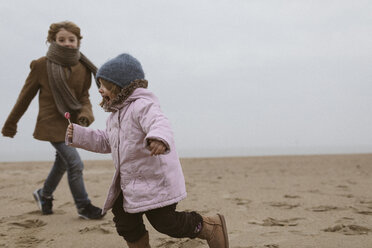 Screaming little girl with lolly running on the beach in winter while her brother watching her - KMKF00096