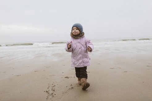 Germany, North Sea Coast, little girl with lolly strolling on the beach in winter - KMKF00099