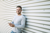 Portrait of laughing man with smartphone - RAEF01954