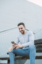 Laughing man sitting on stairs looking at cell phone - RAEF01957