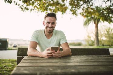 Portrait of relaxed man with cell phone outdoors - RAEF01960