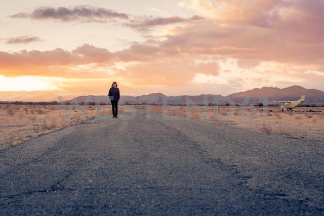 USA, California, Joshua Tree, young guy walks along a road while sunset - WVF00856 - Valentin Weinhäupl/Westend61