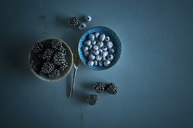 Bowl of blueberries and bowl of blackberries on blue ground - ASF06139