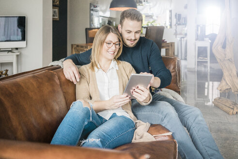 Smiling couple sitting on couch at home sharing tablet - MOEF00581