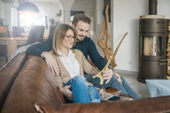 Smiling couple sitting on couch at home with tablet and Eiffel tower model - MOEF00584