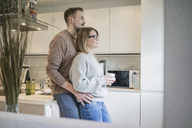 Affectionate couple standing in kitchen at home - MOEF00587