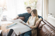Couple sitting on couch at home looking at world map - MOEF00590