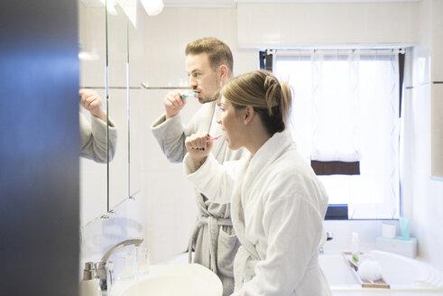 Couple brushing their teeth in bathroom at home - MOEF00596