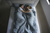 Top view of affectionate couple lying in bed at home - MOEF00611