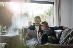 Smiling couple lying on couch at home sharing tablet - MOEF00623