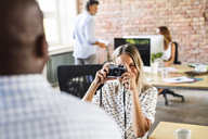 Businesswoman with camera taking picture of colleague in office - HAPF02616