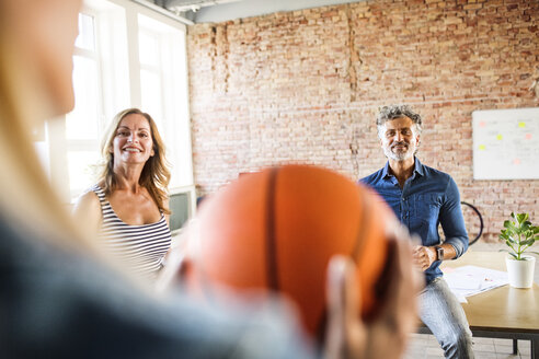 Smiling colleagues with basketball in office - HAPF02622