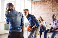 Colleagues playing basketball in office - HAPF02628