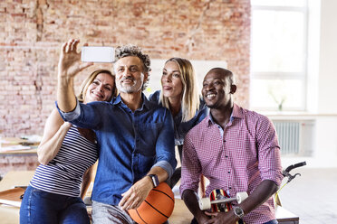 Happy colleagues with basketball in office taking a selfie - HAPF02631