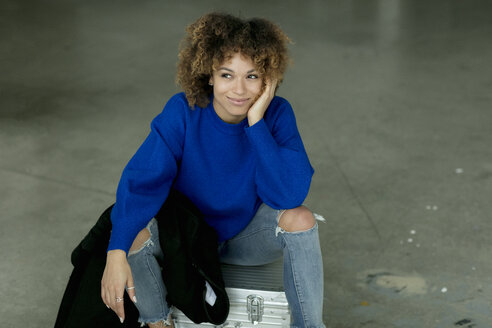 Portrait of smiling woman wearing blue pullover sitting on suitcase - HHLMF00032