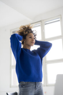 Portrait of young woman doing stretching exercise in office - HHLMF00041