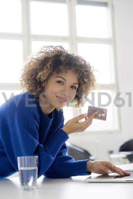Portrait of smiling woman using credit card for paying her online order - HHLMF00044