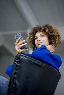 Portrait of smiling woman with cell phone sitting on armchair - HHLMF00050