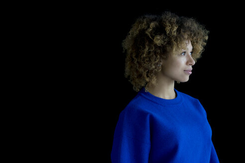 Portrait of woman wearing blue pullover in front of black background - HHLMF00053