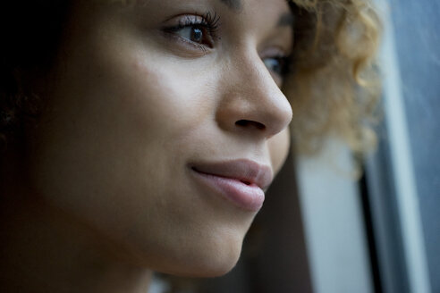 Portrait of smiling woman looking out of window - HHLMF00056