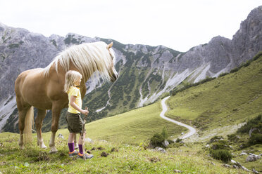 Austria, South Tyrol, young girl with horse on meadow - FKF02867
