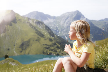 Austria, South Tyrol, young blond girl blowing blowball - FKF02870