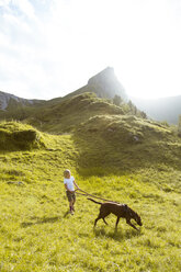 Austria, South Tyrol, young girl hiking with dog - FKF02873