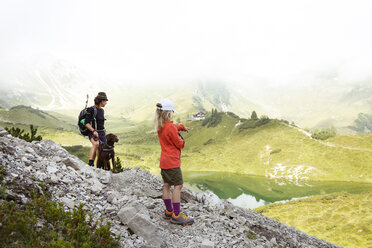 Austria, South Tyrol, mother, daughter and dog on hiking trail - FKF02882