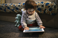 Baby girl watching videos on a tablet at home - GEMF01838