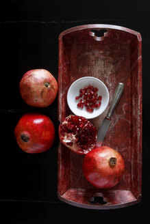 Whole pomegranate and pomegranate seed with bowl and knife on wooden tray - JTF00879