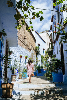 Morocco, Chefchaouen, back view of woman walking alley upstairs - KIJF01809