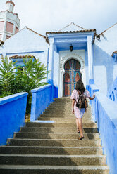 Morocco, Chefchaouen, back view of woman with backpack walking upstairs - KIJF01812