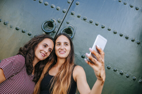 Morocco, Chefchaouen, portrait of two women taking selfie with smartphone in front of green gate - KIJF01815
