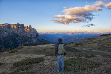 Italy, South Tyrol, Seiser Alm, Hiker in front of Schlern at sunrise - LOMF00677