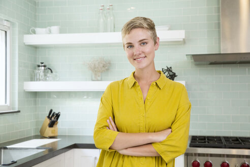 Portrait of smiling young woman in kitchen - MFRF01067