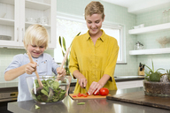 Smiling mother and son preparing salad in kitchen together - MFRF01070