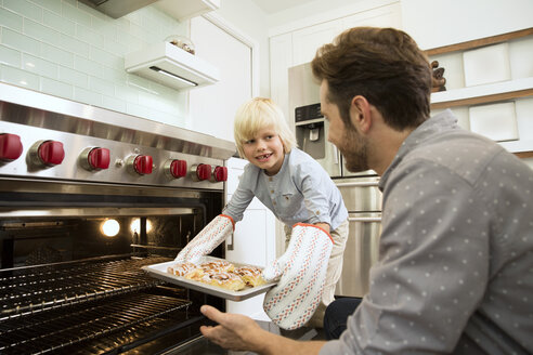Smiling boy taking baking tray out of the oven with father watching him - MFRF01076