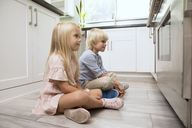 Brother and sister sitting on the floor in kitchen looking at oven - MFRF01079
