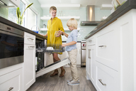 Boy helping mother clearing the dishwasher in kitchen - MFRF01082