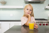 Portrait of pensive girl in kitchen with glass of orange juice - MFRF01085