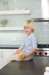 Happy boy in kitchen with glass of orange juice - MFRF01088