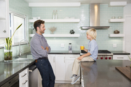 Father and son in kitchen with glass of orange juice - MFRF01091