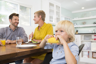 Boy eating corn cob in kitchen with parents in background - MFRF01097