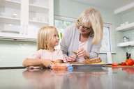 Grandmother and granddaughter preparing lunch box in kitchen together - MFRF01100